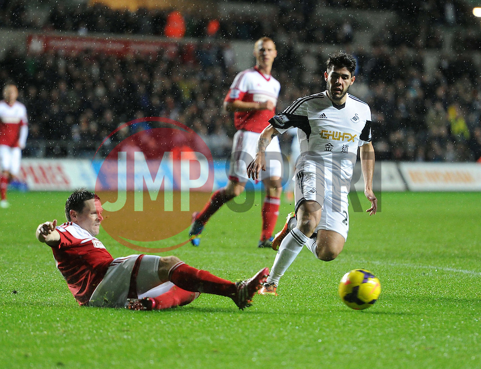 Fulham's Sascha Riether slides the ball away from Swansea City's Jordi Amat - Photo mandatory by-line: Alex James/JMP - Tel: Mobile: 07966 386802 28/01/2014 - SPORT - FOOTBALL - Liberty Stadium - Swansea - Swansea City v Fulham - Barclays Premier League