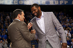 UK Athletic Director Mitch Barnhart, left, presents Walter McCarty member of the 1996 NCAA Championship Team a ring for the accomplishment. The University of Kentucky Men's Basketball team hosted Mississippi State , Wednesday, Feb. 27, 2013 at Rupp Arena in Lexington .