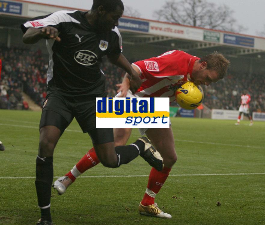 Photo: Mark Stephenson.<br />Cheltenham Town v Bristol City. Coca Cola League 1. 23/12/2006.<br />Chelenham's Michael Townsend hog's the ball with City's Enoch Showunmi.