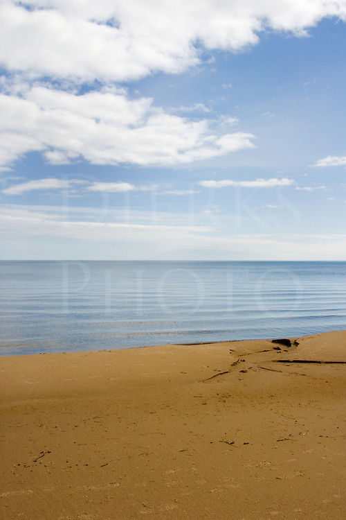 Full view of beach and calm water under blue skies like the beginning of time, Lake Michigan on the Upper Peninsula, Great Lakes.