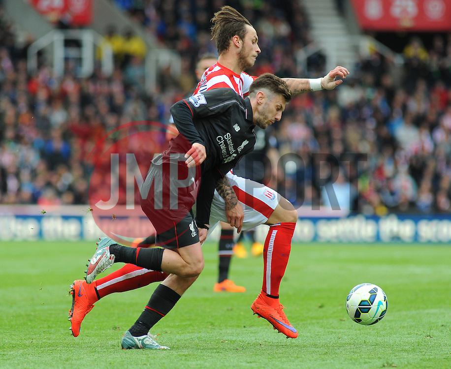 Stoke City's Marko Arnautovic and Liverpool's Adam Lallana battle for the ball - Photo mandatory by-line: Nizaam Jones/JMP - Mobile: 07966 386802 - 24/05/2015 - SPORT - Football - Stoke - Britannia Stadium - Stoke City v Liverpool - Barclays Premier League