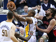 April 09, 2012; Indianapolis, IN, USA; Indiana Pacers power forward David West (21) takes the ball to the hoop as he is guarded from behind by Toronto Raptors center Aaron Gray (34) at Bankers Life Fieldhouse. Mandatory credit: Michael Hickey-US PRESSWIRE
