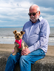 Edinburgh, Scotland, 03 May 2019. Pictured: Tuppence (Tuppy) with Ian, who worked at the Edinburgh Dog & Cat Home for 38 years at the mural unveiling. Tuppy is a Yorkshire terrier who Ian rescued from the home 9 years ago. The 80 foot mural is unveiled today as a colourful addition to Seafield promenade. It is designed and painted by local artists Studio N_Name. It depicts the people, heritage and environment of the local community and features flora, fauna and historic elements of the local coastline. It has been made possible through through partnership with Edinburgh Shoreline Project. It is on the seafront wall of the dog & cat home which rescues, reunites and rehomes lost, stray and abandoned dogs and cats across Edinburgh and the Lothians, caring for 2,367 dogs and 771 cats in 2018.<br /> Sally Anderson | EdinburghElitemedia.co.uk
