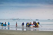 Fishermen arriving at the beach with fishing, and buyers collecting the product .  Manta. Ecuador.