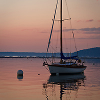 "An anchored sailboat and sunrise reflected in the calm waters of Frenchman's Bay, Bar Harbor, Mt. Desert Island, Maine.  The ""Bar"" and Bar Harbor are seen in the background."
