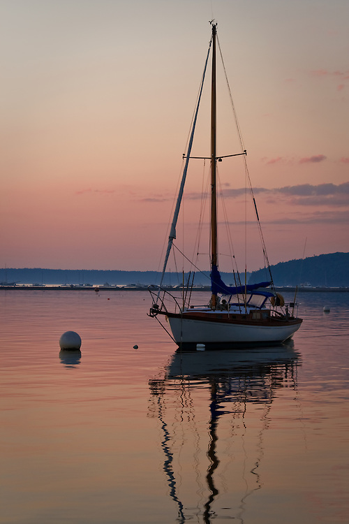 """An anchored sailboat and sunrise reflected in the calm waters of Frenchman's Bay, Bar Harbor, Mt. Desert Island, Maine.  The """"Bar"""" and Bar Harbor are seen in the background."""