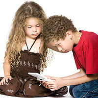 caucasian little boy and girl playing console game isolated studio on white background
