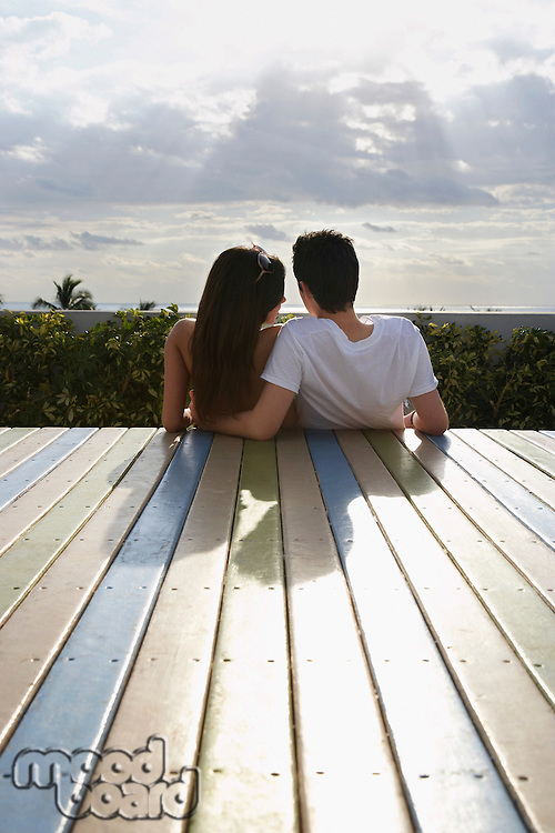Teenage couple (16-17) sitting on wooden deck looking at view back view