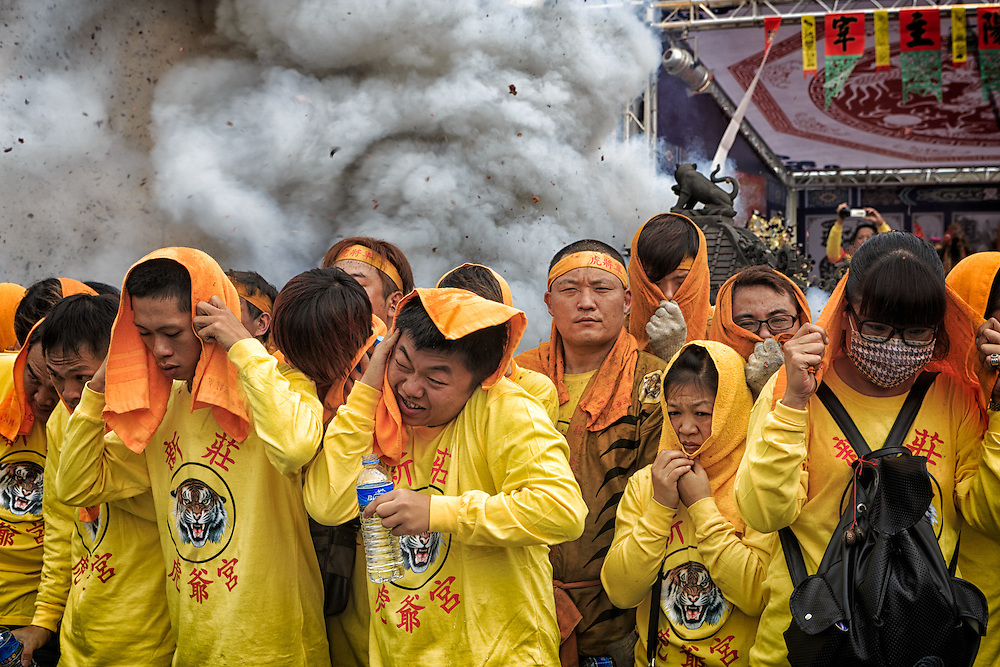 Firecrackers are set off under a God palanquin that is protected by its custodians.