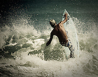 A surfer in action at Kuta Beach, Bali, Indonesia, Southeast Asia.
