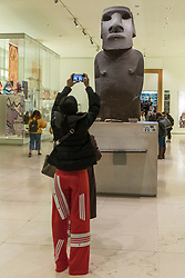 "© Licensed to London News Pictures. 21/11/2018. LONDON, UK.  A members of the public photographs the Hoa Hakananai'a (""Stolen or Hidden Friend"") at the British Museum.  The four-tonne statue, or ""moai"", one of hundreds originally found on Easter Island, has been on display in the museum for 150 years, after it was taken without permission in 1868 by the British naval captain Richard Powell, and given to Queen Victoria.  Tarita Alarcon Rapu, the governor of Easter Island, has demanded that the statue be returned to the island and to the indigenous people, the Rapa Nui.  Photo credit: Stephen Chung/LNP"