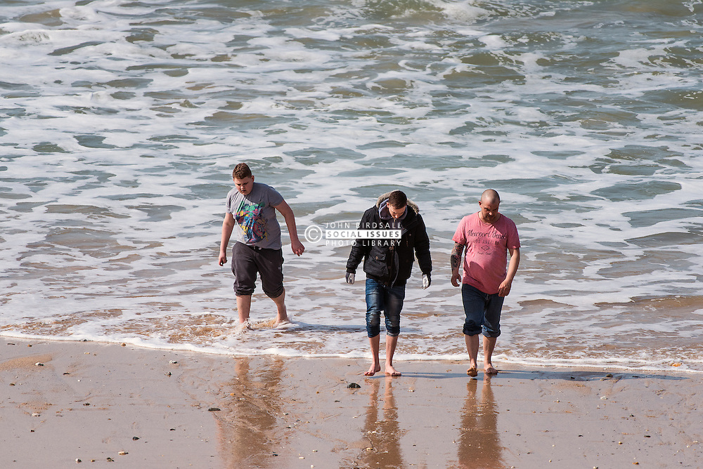 Three men paddling on Fistral Beach in Newquay, Cornwall.