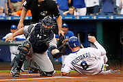 Kansas City Royals' Mike Moustakas (8) scores from second base as New York Yankees catcher Brian McCann catches a late throw in the first inning of a baseball game at Kauffman Stadium in Kansas City, Mo., Friday, May. 15, 2015. Moustakas scored off a Lorenzo Cain double. (AP Photo/Colin E. Braley)
