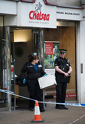 "© London News Pictures. 07/05/2013. Sunbury-On-Thames, UK. A Police scientific support officer outside Chelsea Building Society in Sunbury-on-Thames, in Surrey, which was robbed earlier today (Wed). 55-year-old escaped prisoner Michael Wheatley AKA ""Skull Cracker"", who was arrested in east London, is alleged to have carried out the robbery. Photo credit: Ben Cawthra/LNP"