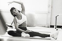 Woman doing floor exercises in gym, portrait (B&W, grainy)