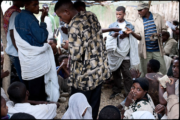 """Guests of two early marriages shall pay money as a sign of respect and gifts for the child brides' families, just after the religious function. North West of Ethiopia, on saturday, Febrary 14 2009.....In a tangled mingling of tradition and culture, in the normal place of living, in a laid-back attitude. The background of Ethiopia's """"child brides"""", a country which has the distinction of having highest percentage in the practice of early marriages despite having a law that establishes 18 years as minimum age to get married. Celebrations that last days, their minds clouded by girls cups of tella and the unknown for the future. White bridal veil frame their faces expressive of small defenseless creatures, who at the age ranging from three to twelve years shall be given to young brides men adults already...To protect the identities of the recorded subjects names and specific places are fictional."""