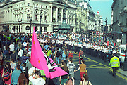 Ravers marching with the Liberty flag through Piccadilly Circus.First Criminal Justice March, Trafalgar Square, London, UK, 1st of May 1994.