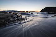 The sea withdraws on the beach after a wave, and leaves a pattern in the sand | Sjøen trekker seg tilbake etter en bølge på stranden og etterlater seg mønster i sanden.