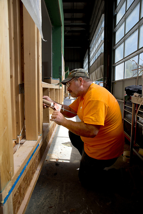 "To help with its weatherization, laborer Tim Nunn caulks electrical boxes from the outside on one of the modular homes under construction at Vermod Homes in Wilder, Vt., on Aug. 28, 2017. ""I haven't seen a house as energy efficient as these,"" he said. (Photo by Geoff Hansen)"