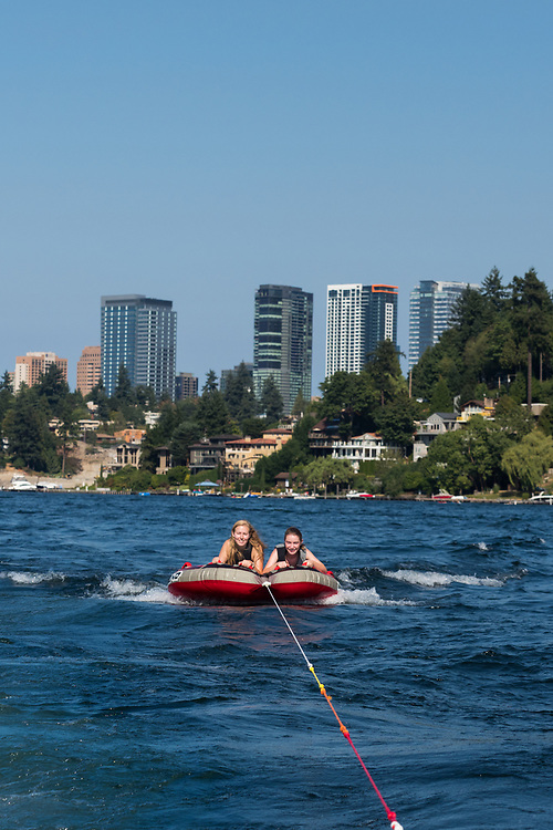 MR United States, Washington, Bellevue. Two teenage girls tubing, or biscuiting, behind a motorboat on Lake Washington with Bellevue skyline.