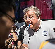 England manager Roy Hodgson holds a pen in his mouth as he uses another to sign autographs as he is mobbed by fans as the team depart for a tour of Manaus ahead of the England open training session at Arena da Amazonia, Manaus, Brazil.  Hodgson purposefully went straight to the fans and spent about 10 minutes getting his picture taken, signing autographs and being generally very approachable and very good humoured. The mainly Brazilian crowd were extremely enthusiastic.<br /> Picture by Andrew Tobin/Focus Images Ltd +44 7710 761829<br /> 13/06/2014