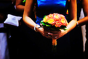 Red and yellow bridal bouquet against a blue dress.