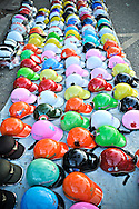 Multi-colored crash helmets are lined up on a Hue sidewalk, Vietnam, Southeast Asia