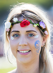 © Licensed to London News Pictures. 05/05/2018. Chalton, UK. 28 year old Sara Miles from Havant wears flowers in her hair as she enjoys the sunshine during the Beltain Festival at Butser Ancient Farm in Hampshire. Over two thousand people have gathered to witness the ancient Celtic celebration of summer - which culminates in the burning of a giant Wickerman figure  Photo credit: Peter Macdiarmid/LNP