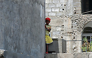 A young girl peers shyly from behind a building wall, Assomada, Santiago, Cape Verde (Cabo Verde). Assomada lies on a plateau in central Santiago.