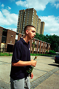 Bored teenage boy drinking a bottle of wine outside on a housing estate Lambeth Walk South London c.2000