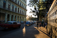 A man holds hands with a young girl, leaning down to listen to her as they walk in Havana, Cuba