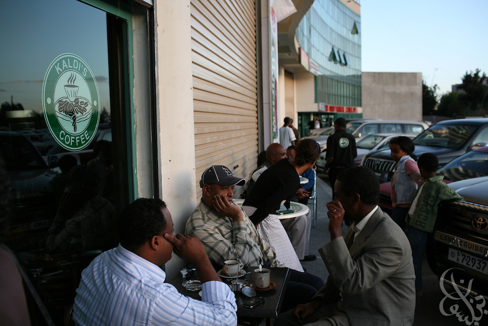 "Ethiopian men enjoy a coffee at the local Ethiopian coffee chain ""Kaldi's Coffee"" February 20, 2007 in Addis Ababa.  Kaldi's is inspired by the international coffee chain, Starbucks, and it's logo and store locations look nearly identical."