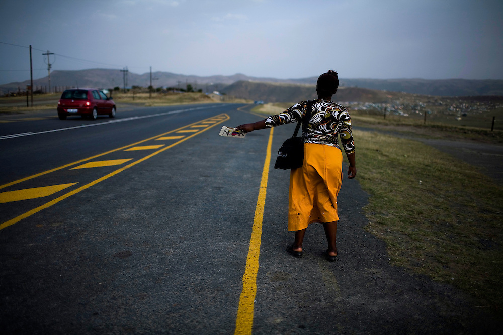 A woman stands on the side of the road and hitchikes in Eastern Cape. Many migrant workers from Eastern Cape go to work in the mines. South African Gold miners are particularly vulnerable to contracting TB because of the small, poorly ventilated work conditions, high rates of TB and high rates of silicosis, a lung disease often found in miners that increases the chance of catching TB.