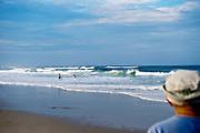 Mature man watches surfers, Cape Cod National seashore, Cape Cod, MA