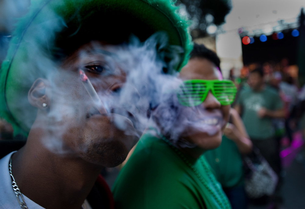 Guss Hall puffs on a cigarette as Nich Ramirez, a friend displays his eyewear during St. Patrick's Day,  at the blocked off part of downtown on L st. to celebrate St. Patrick's Day.March 17, 2010