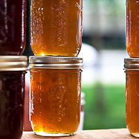 Jars of colorful home-made jams and jellies glowing in the sun.