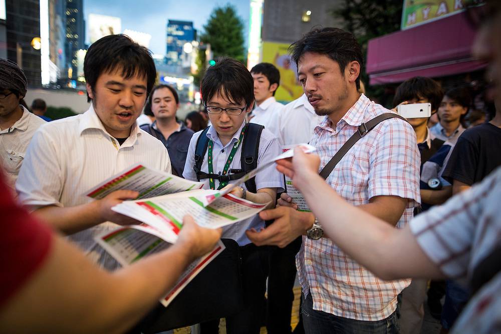 TOKYO, JAPAN - JULY 20 : Supporter of candidate Mac Akasaka handed campaign leaflets to people while he delivers his campaign speech on stage for the July 31 Tokyo gubernatorial election in Shinjuku, Tokyo, Japan on Wednesday, July 20, 2016.   (Photo: Richard Atrero de Guzman/NUR Photo)