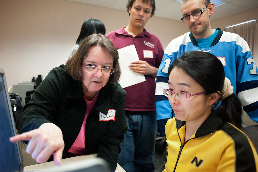 From right to left: Suzanne Freeland James Dutti and Luke Gregory help Zhengfang Wang fill out her taxes during a vita tax session put on by the college of business to assist international students in filing their taxes on March 29th 2013. Photo by: Ross Brinkerhoff.