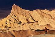A photographer shoots Zabriskie Point at sunrise.  Death Valley National Monument, California/ Nevada. USA.
