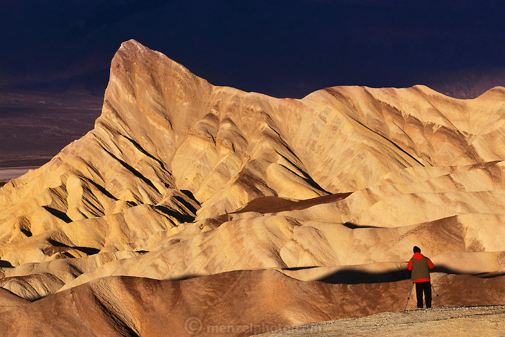 A photographer shoots Zabriskie Point at sunrise.  Death Valley National Monument, California/ Nevada. USA.