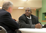 Lloyd Smith (from right) of Cedar Rapids talks with Dennis Larkin, Branch Manager of the Cedar Rapids Office of the Small Business Administration, during a meeting of RED-I at the African American Museum of Iowa in Cedar Rapids on Thursday, December 12, 2013.