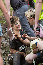 © Licensed to London News Pictures 26/05/2018, brockworth, Gloucester, UK. The annual cheese rolling race held at Coopers Hill, Brockworth outside Gloucester. Competitors race down the extremly steep slippery hill chasing a double Gloucester cheese, the winner of each race recieves the cheese as thier prize. Pictured here :  The winner of the ladies race Flo Early being attended to for a shoulder injury after winning the ladies race - Photo Credit : Stephen Shepherd/LNP