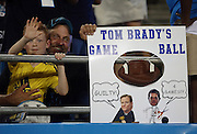 """A fan holds onto a """"Tom Brady's Game Ball"""" sign showing a deflated football and alluding to his four game suspension as part of the Deflategate scandal during the New England Patriots 2016 NFL preseason football game against the Carolina Panthers on Friday, Aug. 26, 2016 in Charlotte, N.C. The Patriots won the game 19-17. (©Paul Anthony Spinelli)"""