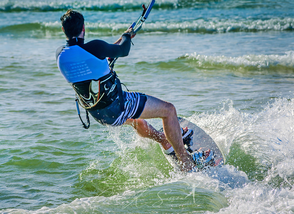 Mathieu Junco kitesurfs, October 18, 2015, in Dauphin Island, Alabama. Junco, from France, began kitesurfing five years ago. Windy conditions on the island brought surfers out in droves, but many, like Junco, found that the brisk northerly winds made kitesurfing challenging on the south side of the island. Kitesurfing began in France in the 1980's and became a mainstream water sport in 1999, combining aspects of wakeboarding, windsurfing, surfing, and paragliding. More than 1.5 million people participate in the global sport. (Photo by Carmen K. Sisson/Cloudybright)