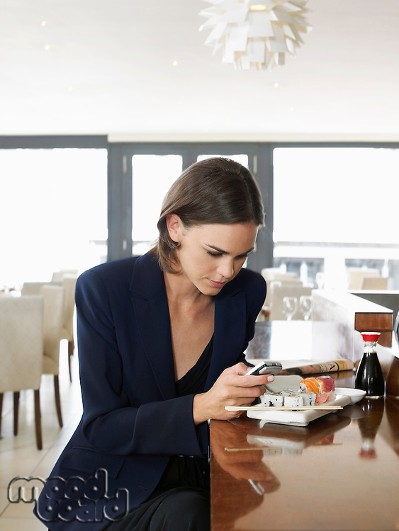 Woman text messaging in sushi restaurant