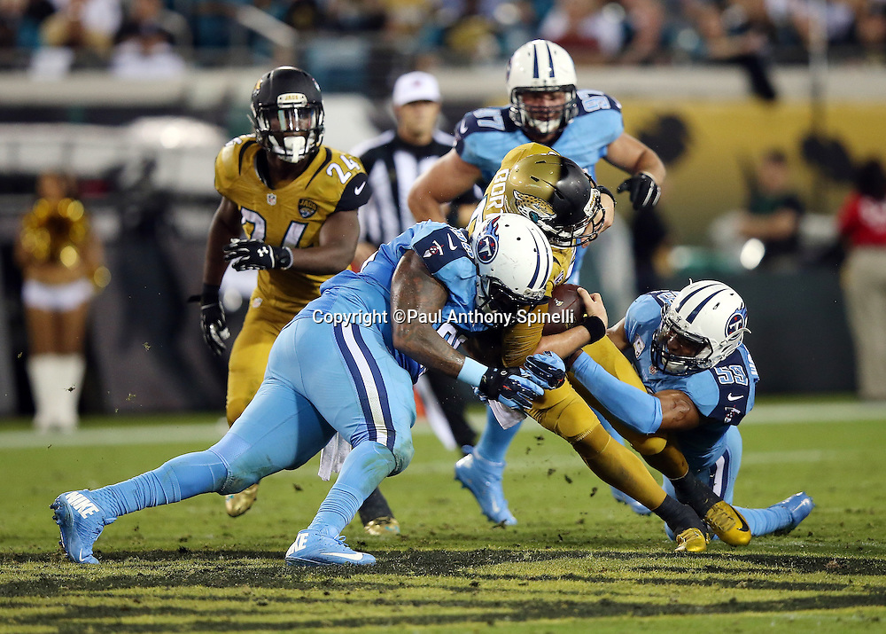 Jacksonville Jaguars quarterback Blake Bortles (5) gets sacked by Tennessee Titans inside linebacker Wesley Woodyard (59) and Tennessee Titans defensive end Jurrell Casey (99) for a loss of 6 yards in the second quarter during the 2015 week 11 regular season NFL football game against the Tennessee Titans on Thursday, Nov. 19, 2015 in Jacksonville, Fla. The Jaguars won the game 19-13. (©Paul Anthony Spinelli)