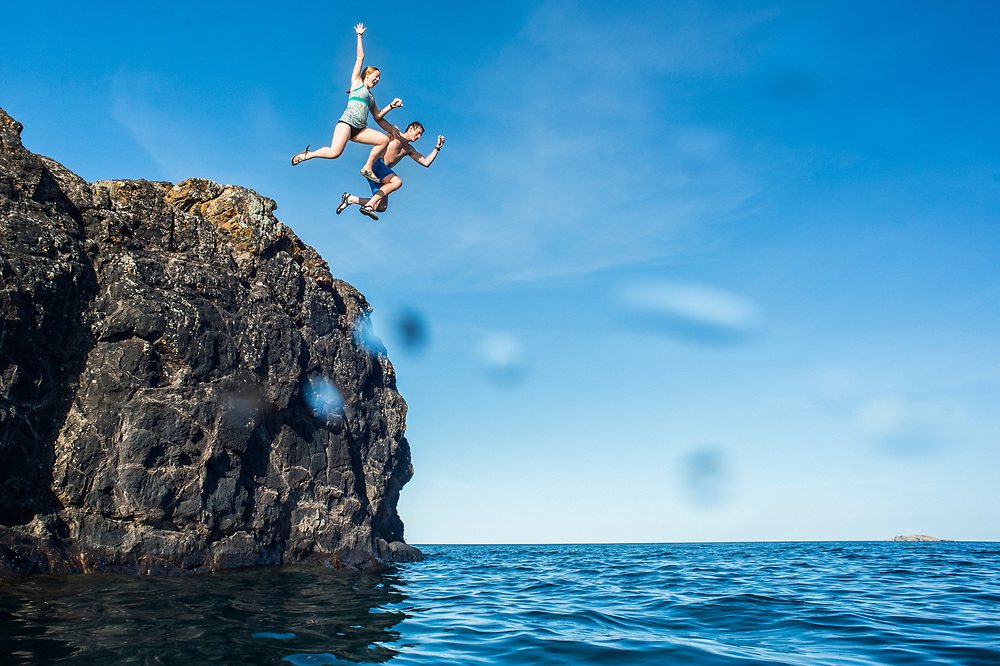 Summer activity at the Black Rocks of Presque Isle Park in Marquette, Michigan. The dark geological feature is a popular place for jumping into Lake Superior.