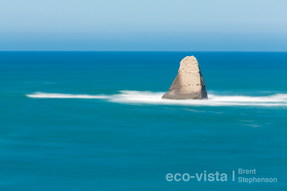 The Shark's Tooth or Pinnacle located just off the tip of Cape Kidnappers is composed of sedimentary mudstones, and is slowly eroding from pounding seas, such as these. Long expsoure during storm surge on a sunny day. Cape Kidnappers, Hawkes Bay, New Zealand. October.