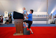 Hilary Tayloe of Denver holds one-year-old Luke Grasso behind a replica of the presidential podium in the American Presidential Experience exhibition on Saturday, August 23rd in Denver, Colorado in advance of the 2008 Democratic National Convention which begins on Monday, August 25.