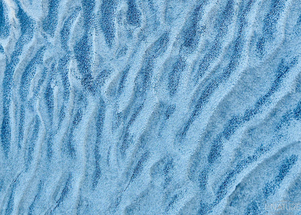 Ridges and waves of sand laid down by wind and water along the Athabasca River near Jasper Alberta. Light and dark blue ridges in sinuous waves.